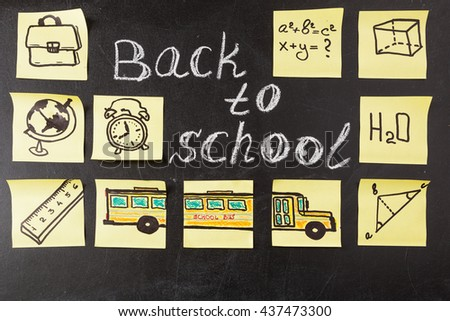 "Back to school background with title ""Back to school"" written by white chalk and images of school bus and school attributes written on the yellow pieces of paper on the black school chalkboard - stock photo"