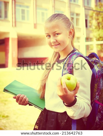 Back to school - beautiful young schoolgirl holding book and apple, education concept