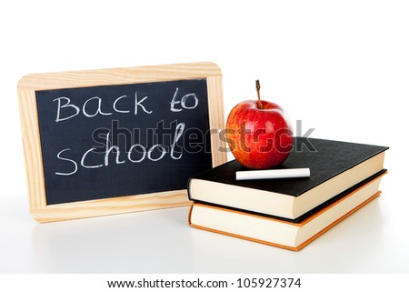 back to school: blackboard slate and stack of books with apple on top over white background - stock photo