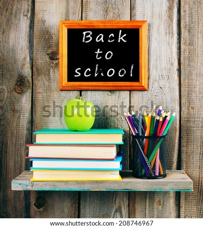 Back to school. Books, an apple and pencils on a wooden shelf.