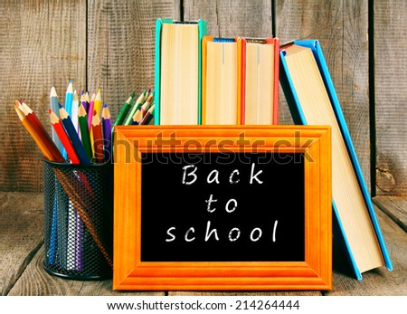Back to school. Books and school tools on a wooden background.