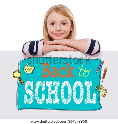 Back to school. Cheerful girl leaning over white board with sketch on it and looking at camera with smile while standing against white background  - stock photo