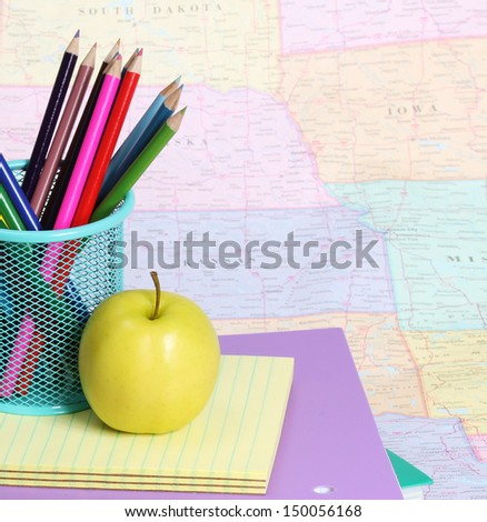 Back to school concept. An apple and colored pencils on pile of books over the map