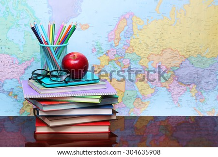 Back to school concept. An apple, colored pencils and glasses on pile of books on desk over map - stock photo