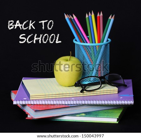 Back to school concept. An apple, colored pencils and glasses on pile of books over black background . The words 'Back to School' written in chalk on the blackboard