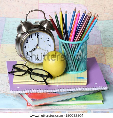Back to school concept. An apple, colored pencils, glasses and alarm clock on pile of books over the map - stock photo