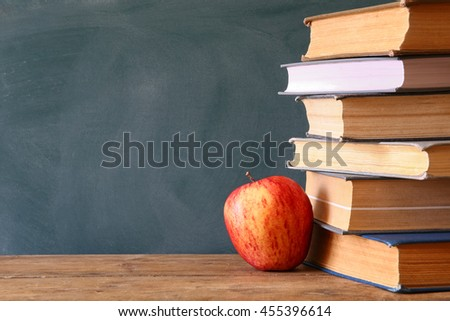 Back to school concept. Blackboard with stack of books and apple on wooden desk. retro filtered