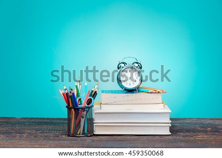 Back to School concept. Books, colored pencils and clock - stock photo