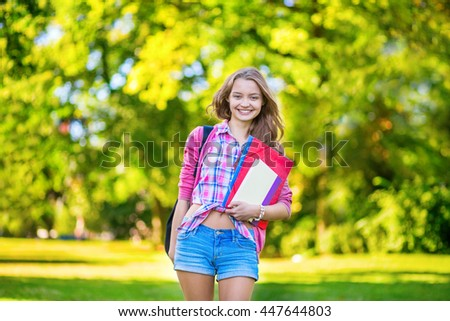 Back to school concept. Cheerful college student in campus, holding books and folders