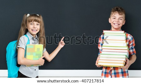 Back to school concept. Happy little girl and boy with books at the black chalkboard in classroom.