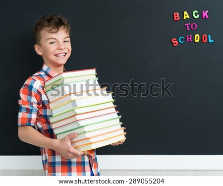 Back to school concept. Happy pupil with books at the black chalkboard in classroom. - stock photo
