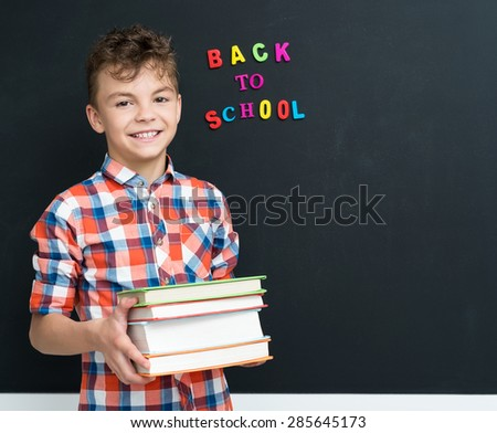 Back to school concept. Happy schoolboy with books at the black chalkboard in classroom.