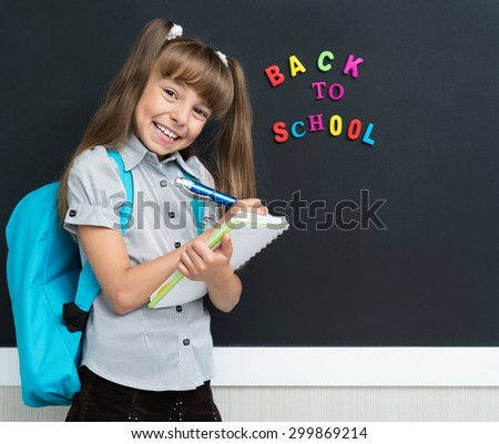 Back to school concept. Happy schoolgirl with backpack and notebook at the black chalkboard in classroom.  - stock photo