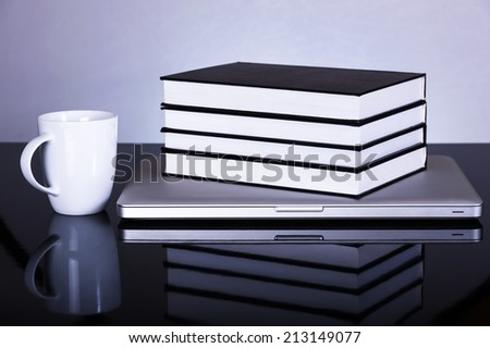 Back to school concept, laptop books coffee mug on reflective surface
