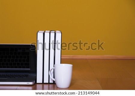 Back to school concept, laptop books coffee mug on wooden floor - stock photo