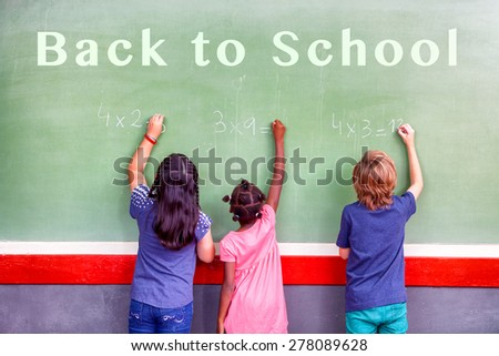 Back to school concept. Multi ethnic classroom writing on chalkboard. - stock photo
