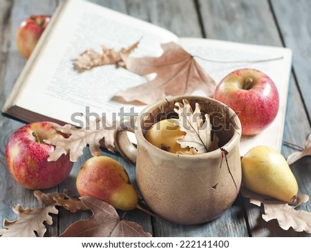 Back to school concept. Old books, apples, pears, fallen leaves and vintage mug on wooden background. - stock photo