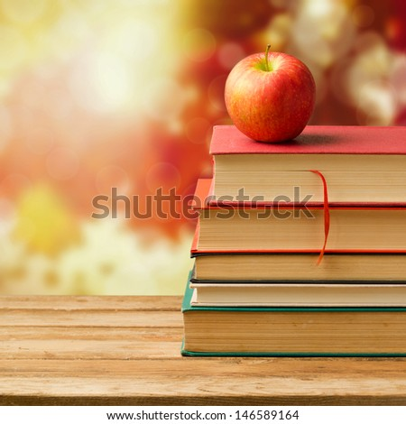 Back to school concept. Old vintage books and apple over autumn leaves bokeh background - stock photo