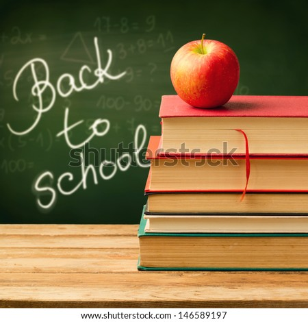 Back to school concept. Old vintage books and apple over chalkboard background