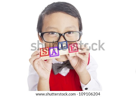 Back to school concept; Portrait of asian elementary school student showing letter blocks spelling out the word SALE. Shot in studio isolated on white