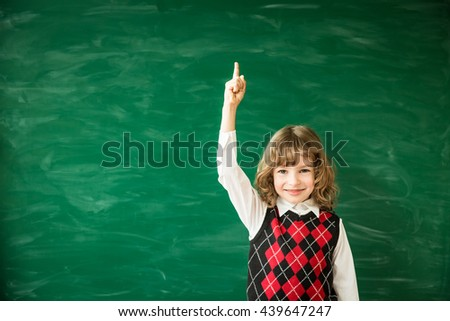 Back to school concept. School child in class. Happy kid against green blackboard. Smart child in classroom. Idea and education concept