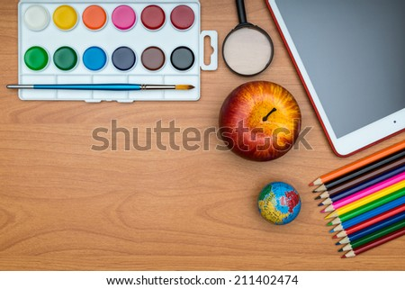 Back to School concept .  School supplies and tablet on wooden school desk from above - stock photo
