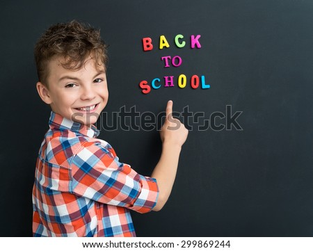 Back to school concept. Schoolboy at the black chalkboard in classroom. - stock photo
