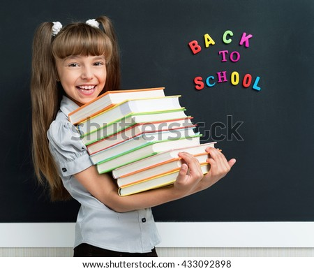 Back to school concept. Schoolgirl with books at the black chalkboard in classroom.