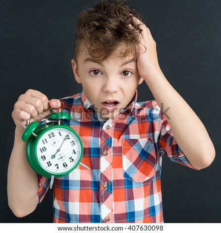 Back to school concept. Shocked pupil with big green alarm clock at the black chalkboard in classroom. - stock photo