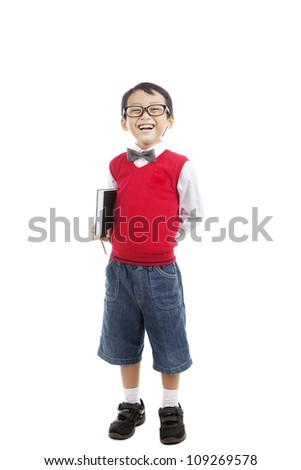 Back to school concept: Smiling elementary school boy holding book and ready for school