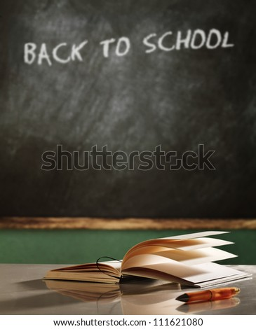 Back to school concept still life with book, pen and  blackboard - stock photo