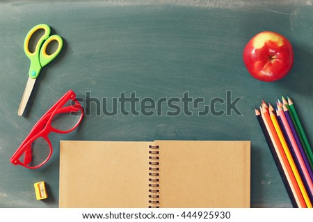 Back to school concept. Top view of school supplies on blank blackboard - stock photo