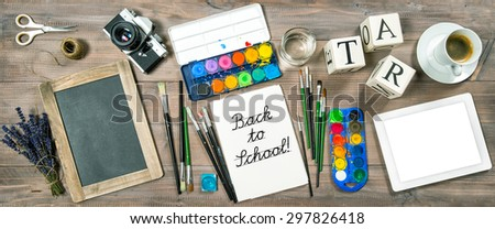 Back to school concept. Watercolor, brushes, digital tablet pc, chalkboard, vintage no name camera, office supplies, tolls and accessories. Retro style toned picture - stock photo