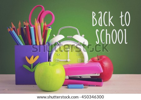 Back to School Concept with classroom desk and bright colored stationery supplies on white wood rustic table and green board background, with added filters and retro hand drawn style text.  - stock photo