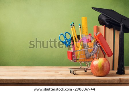 Back to school concept with shopping cart, books and graduation hat