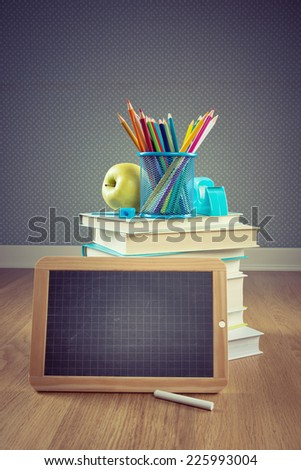 Back to school concept with small chalkboard, apple and colorful stationery. - stock photo