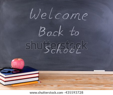 Back to school concept with welcome back to school message on erased black chalkboard plus desktop and supplies.