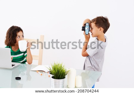 Back to School. Couple of kids. He is taking some pics while she is doing her homework - stock photo