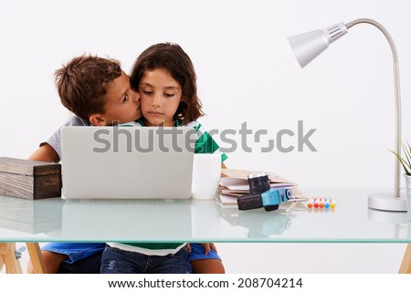 Back to School. Couple of lovely kids kissing while doing some homework - stock photo