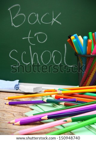 Back to school. Different school accessories against a school board. - stock photo