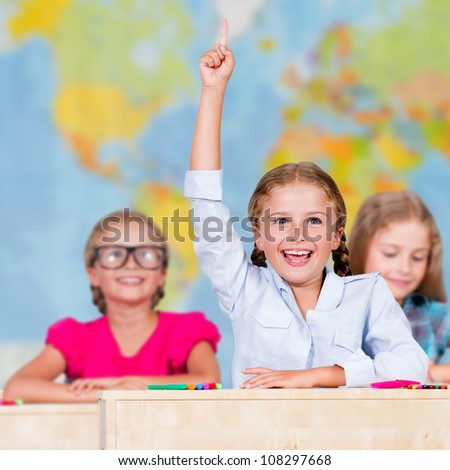 Back to school - elementary school pupil raising hand - stock photo