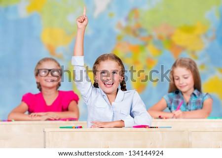 Back to school - elementary school pupil raising hand - stock photo