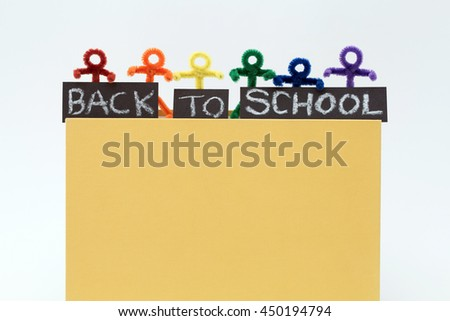 Back to school fun. Rainbow pipe cleaner people holding words of back to school while standing on a yellow book. A simple educational photo for a variety of ideas. Horizontal with copy space. - stock photo