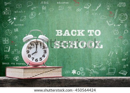 Back to school: Green chalkboard background for announcement w/ wake up alarm clock & textbook on grunge old dark wood top+ copyspace: Students' educational time for learning system concept - stock photo