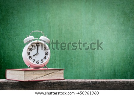 Back to school: Green chalkboard background for announcement w/ wake up alarm clock & textbook on grunge old dark wood table top+ copyspace: Students' educational time for learning system concept - stock photo