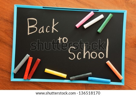back to school, hand writing on chalkboard - stock photo
