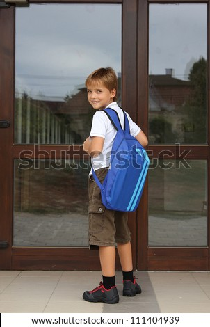 Back to school - happy young boy standing in front of the entrance of the school - school concept