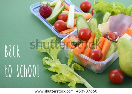 Back to school healthy school lunch box on green background, closeup with sample text.  - stock photo