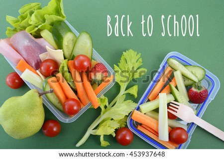 Back to school healthy school lunch box on green background with sample text.  - stock photo