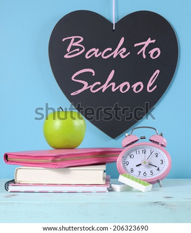 Back to School heart blackboard with bright pink and colorful stationery, green apple and pink clock on pale blue background. - stock photo